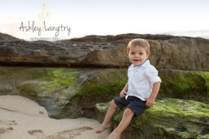 baby boy poses on green rock