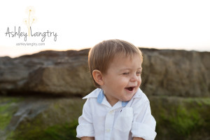 boy laughs and giggles while on rock