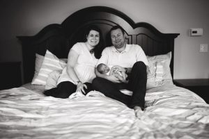black and white image of family in bed with newborn baby